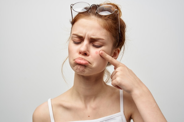 Woman with a pimple on the face hygiene treatment