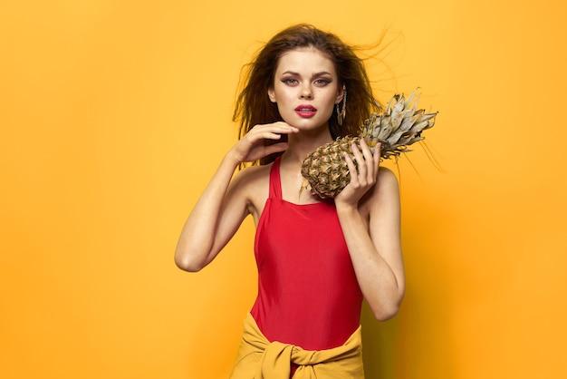 Женщина с ананасом в руках белая футболка экзотические летние развлечения желтый фон