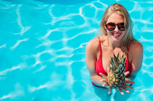 Woman with pineapple in pool with copy space