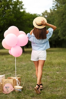 Woman with pink balloons and straw hat in green sunday park