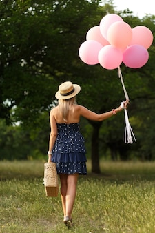 Woman with pink balloons and wicker basket in green sunday park
