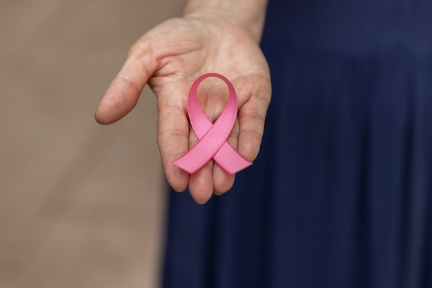 Woman with pink bow on her palm. breast cancer prevention campaign. pink october