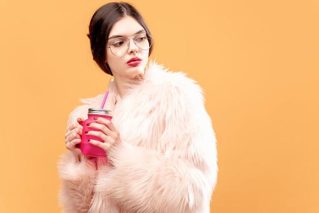黄色にピンクの飲酒瓶を持つ女性