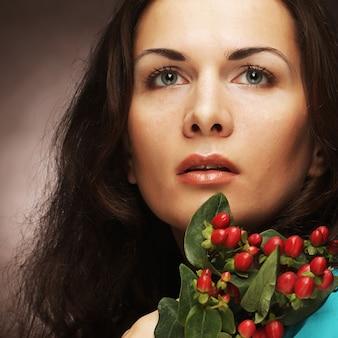 ピンクの花を持つ女性。スタジオショット。