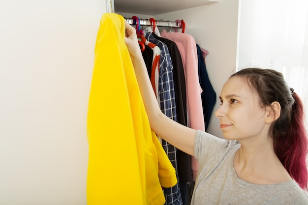Woman with pink hair chooses clothes in closet and takes out yellow hoody, looks at her with smile