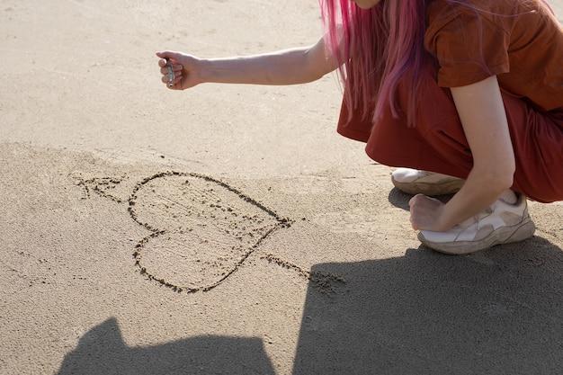 ピンクの髪の女性は砂の上に棒でハートを描く