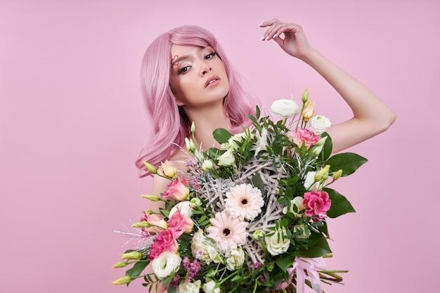 Женщина с розовыми волосами держит букет цветов