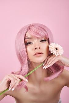 Женщина с розовыми волосами, держа в руке цветок