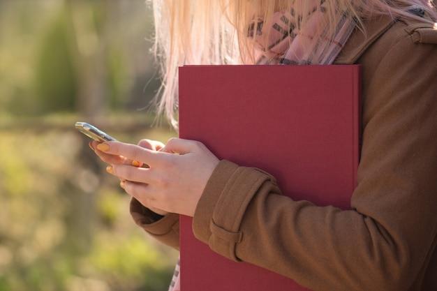 赤い本を持っているピンクの髪の女性