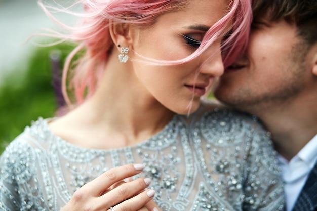 La donna con i capelli rosa si appoggia al suo uomo tenero