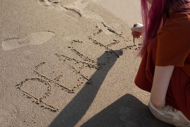 砂の上に棒でビーチでピンクの髪の女性は平和という言葉を書きます