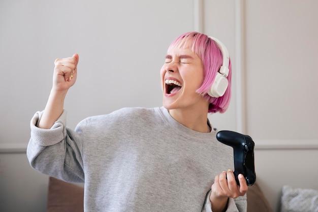 Женщина с розовыми волосами играет в видеоигру