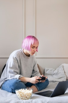 Donna con capelli rosa che gioca con un joystick sul laptop Foto Gratuite