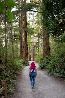 Woman with pink hair walking through the path in the forest