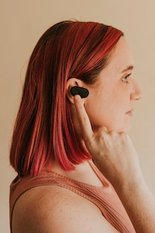 Donna con i capelli rosa che indossa auricolari wireless