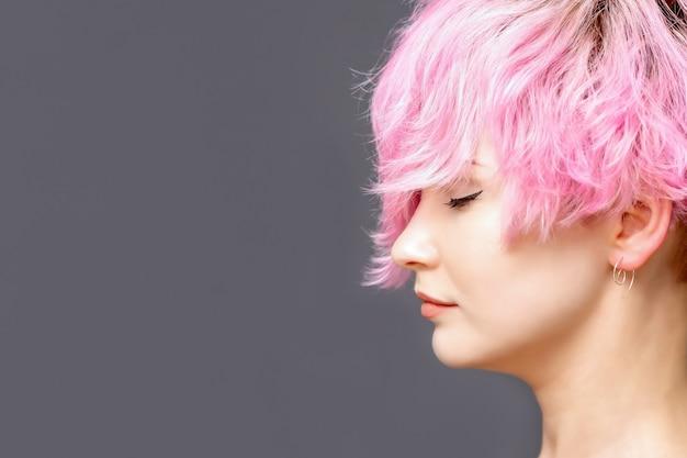 핑크 헤어 스타일을 가진 여자는 닫힌 된 눈 측면보기와 서