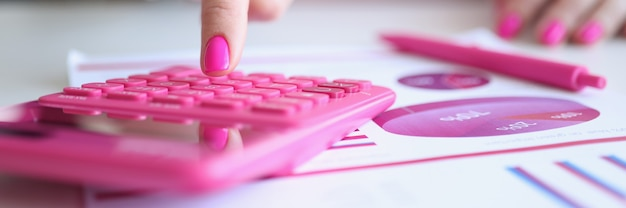 Woman with pink manicure counting on calculator near paper with charts closeup