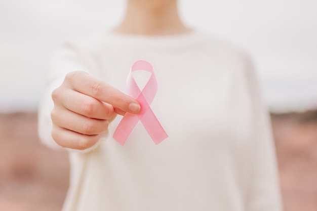 A woman with a pink ribbon, cancer symbol, in her hand