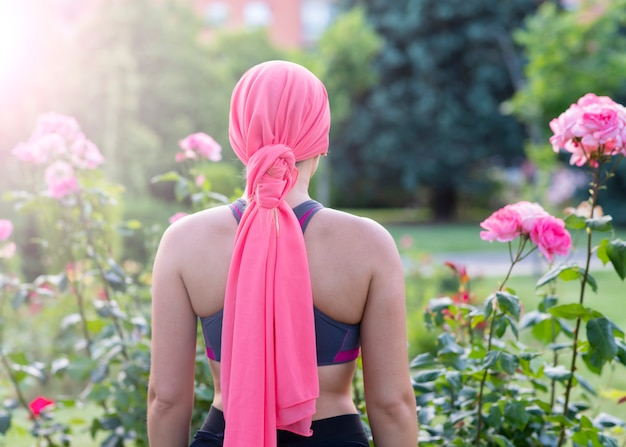 Woman with pink scarf, concept of fight against cancer