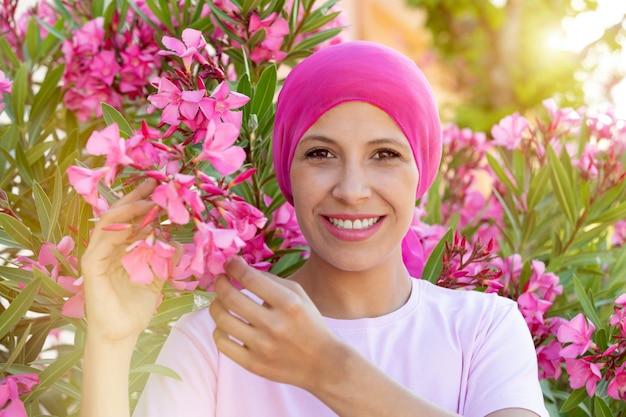 頭にピンクのスカーフを持つ女性。がんの意識
