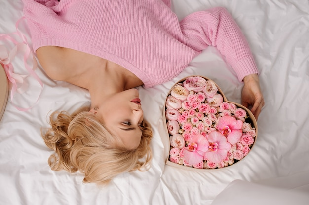 Woman with pink shirt lying on the bed near the heart shape box of rose colored flowers