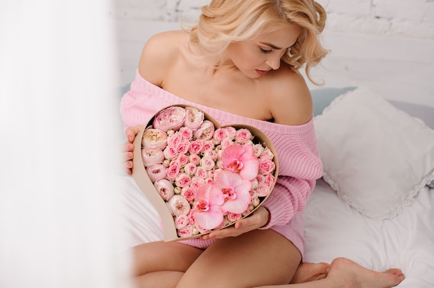 Woman with pink shirt sitting on the bed holding the heart shape box of rose colored peonies, orchids and roses