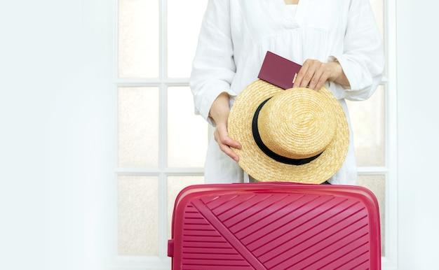 Женщина с розовым чемоданом держит летнюю шляпу и паспорт, стоит у двери и готовится к путешествию.