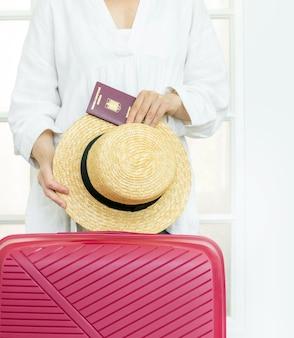 Женщина с розовым чемоданом держит летнюю шляпу и румынский паспорт и готов к путешествию.