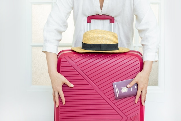 Woman with pink suitcase holds summer hat and romanian passport and ready travel.