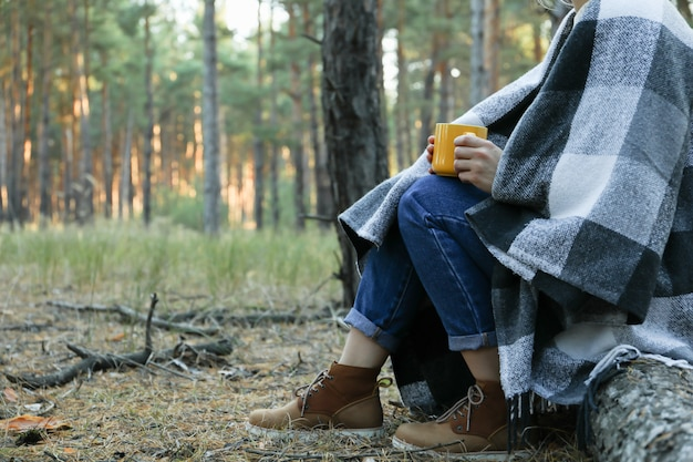 Woman with plaid and cup of hot drink in pine forest, space for text