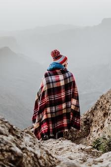 美しい山の風景を見下ろす格子縞のポンチョとポンポンビーニー帽子を持つ女性