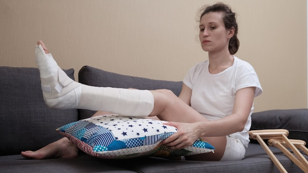 Woman with a plaster cast sits on a sofa, a pillow is placed under a broken leg.