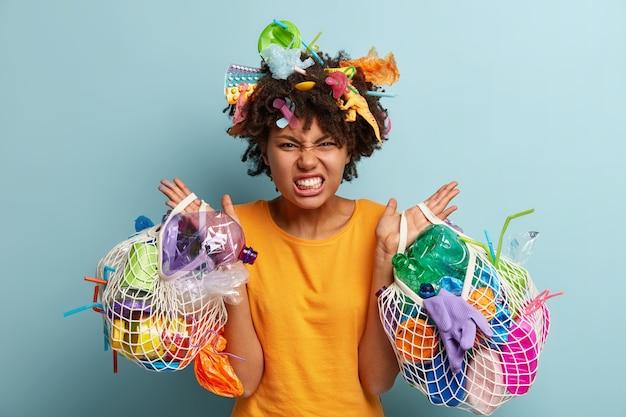 Donna con rifiuti di plastica in borsa a rete