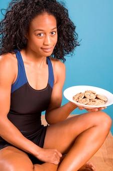 ポストワークアウトクッキーのプレートを持つ女性