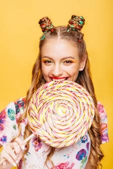 お菓子を食べて遊び心のある表情を持つ女性
