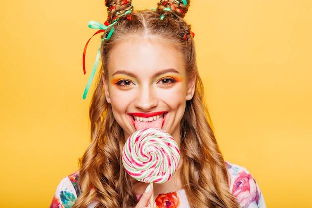 Женщина с игривым взглядом лижет конфету языком