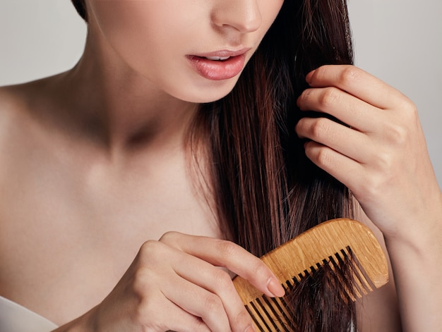 Woman with a playful mood combs her hair with a light brown comb by right hand on the, she holds hair with her left hand