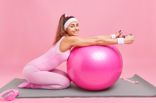 La donna con la coda di cavallo vestita in activewear allena i muscoli allunga l'espansore si appoggia sulla palla fitness pone sulle ginocchia al tappetino ha un corpo sottile flessibile