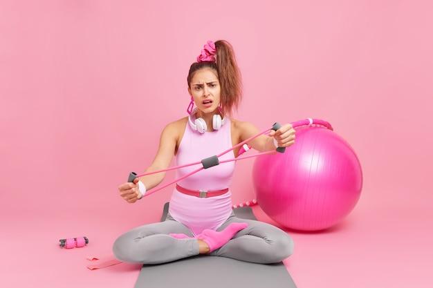 ポニーテールストレッチエキスパンダーを持つ女性は、スポーツウェアに身を包んだ足を組んで座っていますフィットネスマットにフィットボールフラフープ抵抗バンドポーズを使用しています