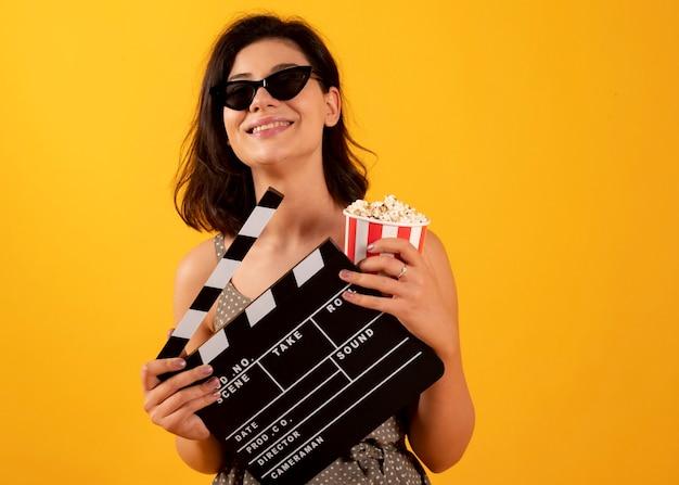 ポップコーングラスとカチンコ映画館を持つ女性