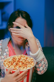 Woman with popcorn sitting on the sofa watching something scary while eating popcorn and being afraid