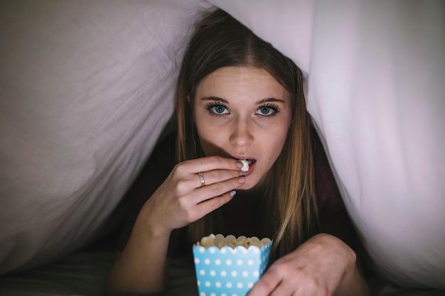 毛布の下で映画を見ているポップコーンを持つ女性