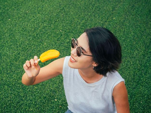 アイスキャンデーを持つ女性。サングラスと緑の草の背景に黄色のアイスキャンデーを保持しているカジュアルな白いノースリーブシャツ、夏の幸せな美しいアジアの女性の短い髪。