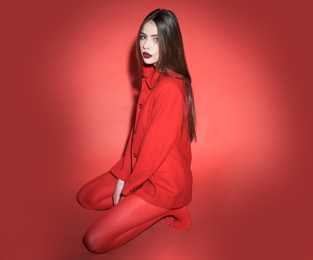 Woman with posing in total red outfit. fashion concept. girl on calm face in red formal jacket and tights, red background. lady looking at camera while sitting on floor. Premium Photo