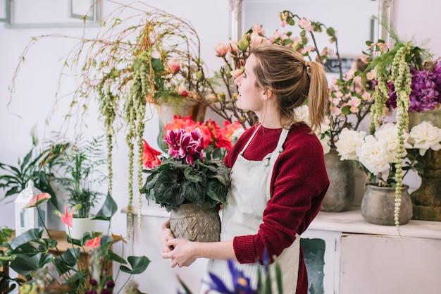 Женщина с горшечным цветком в магазине