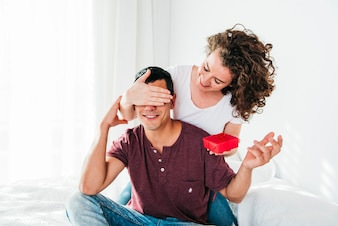 Woman with present closing eyes to smiling man