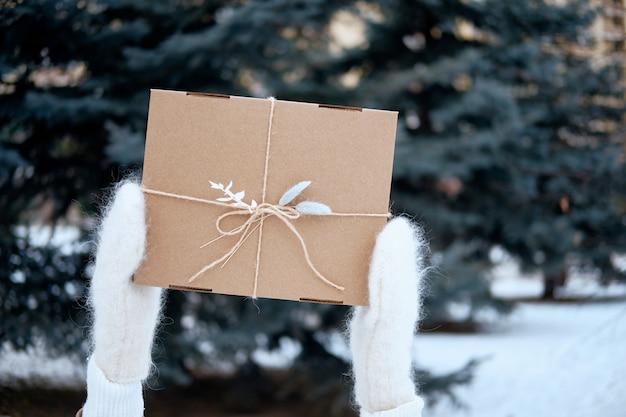 屋外のプレゼントやギフトボックスを持つ女性。ニットミトンの手。スタイリッシュな暖かい服を着てください。