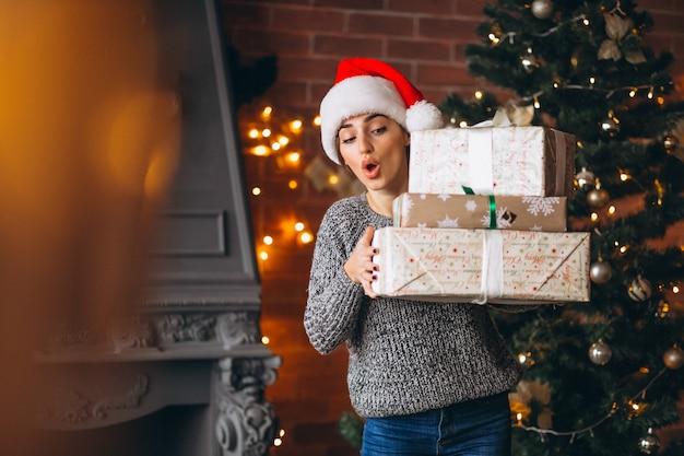 クリスマスツリーの前に立っているプレゼントを持つ女性