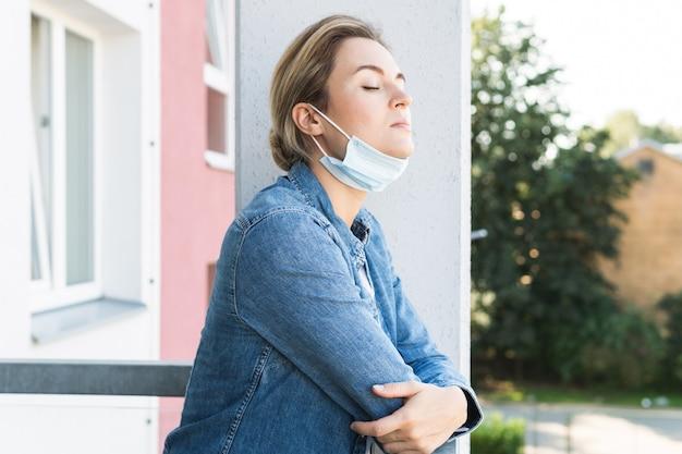예방 마스크를 쓴 여성이 심호흡을 하기 위해 외출하고 있다