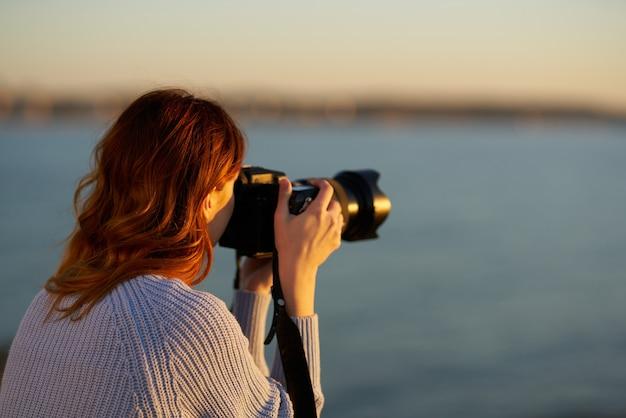 海に沈む夕日にプロのカメラを持つ女性